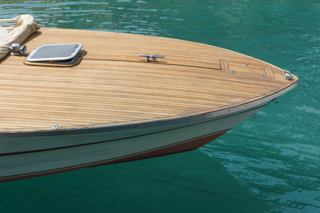 prow: Prow of a motorboat or speedboat with a wood finish moored in a harbor in sheltered water, high angle close up view