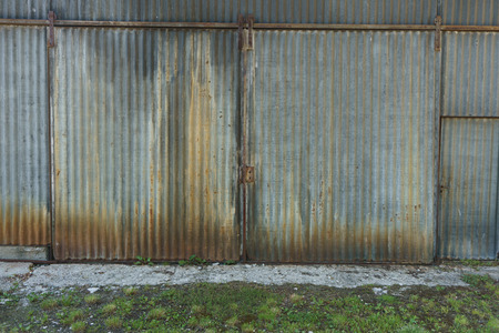 galvanised: Grunge corroded corrugated iron building with rusty closed double doors, close up front view of the exterior facade