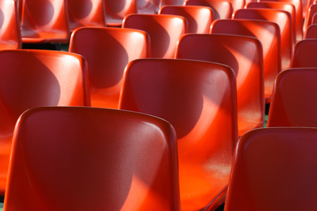 venue: Rows of empty red plastic chairs arranged as seating for an audience in a venue , close up receding view
