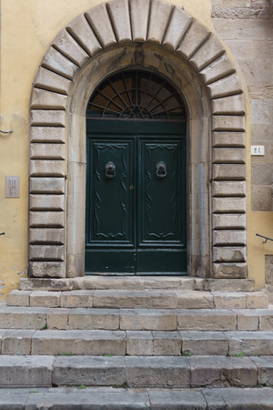 Old arched double wooden door with stone surround and entrance steps in the exterior wall of a building Stock Photo