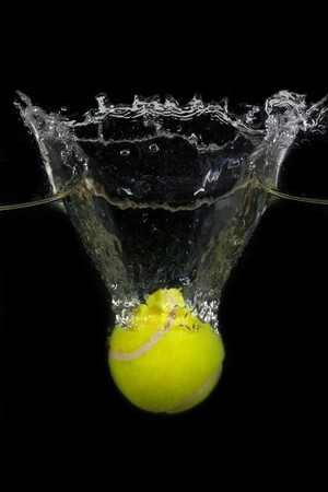 ball aqua: A tennis ball  is dropped into water in front of black background