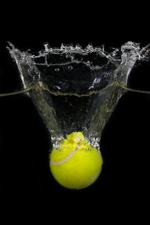 dropped: Una pelota de tenis es caer en el agua delante de fondo negro