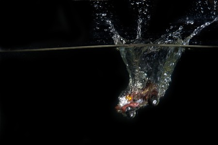 A toy car is dropped into water in front of black background