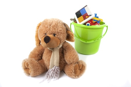A toy bear is in front of a green toy bucket which is full with different and colored toys