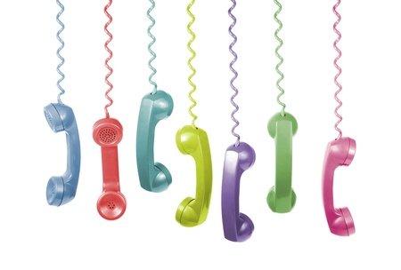telephone cord: Lots of different coloured old phone handsets are hanging on white background