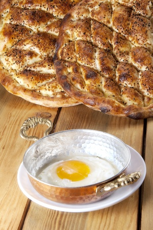 Fried egg in a shallow cooking pan and traditional Turkish breads : Pide