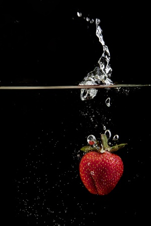 A single fresh strawberry is dropped into water on black background