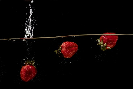 Fresh strawberries are dropped into water on black background photo