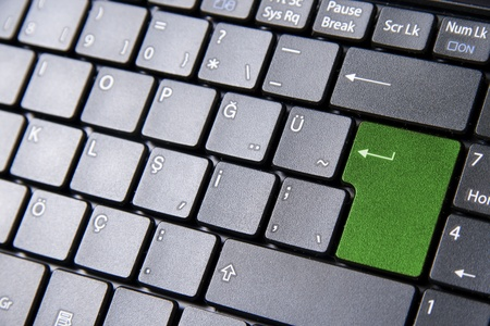 A close up to a laptop keyboard with a green enter key photo