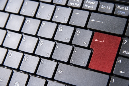 A close up to a laptop keyboard with a red enter key photo