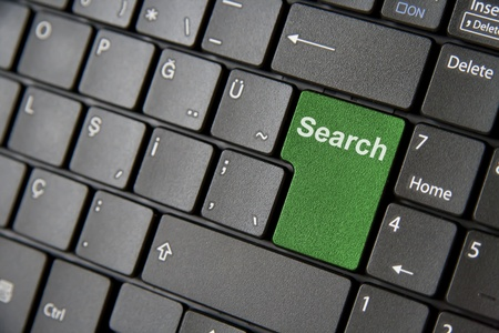 A close up to a laptop keyboard which has a green search key photo