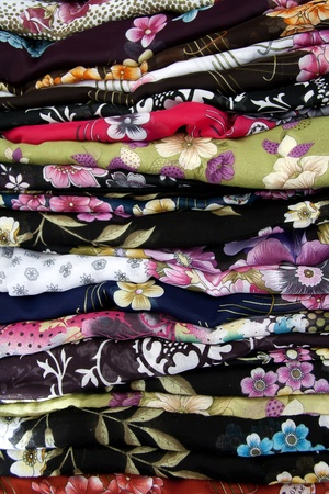 A stack of scarves made by using traditional lithographic painting method photo