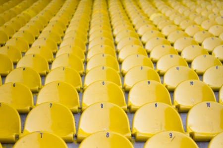 symetric: Empty yellow futboll stadium seats are creating a symetric view Stock Photo