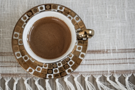 Delicious traditional Turkish coffee served in different golden coffee cup photo