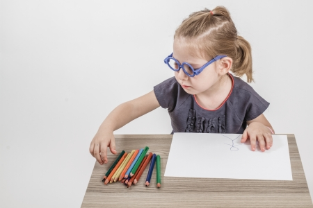 Blond cute little girl with blue glasses painting on a school desk