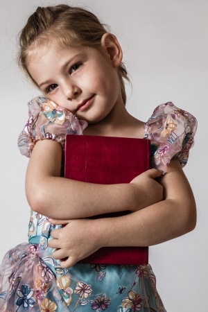 Blond cute little girl hugging a red book  photo