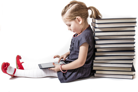 Cute little girl playing with a tablet pc while sitting on encyclopedias