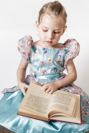 Blond cute little girl reading an old red book photo