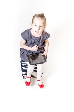 encyclopedias: Ni�a linda que juega con un Tablet PC mientras est� sentado en enciclopedias