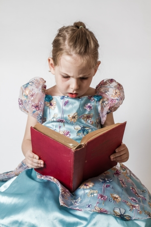 Blond cute little girl reading an old red book Stock Photo - 24119043