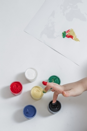 Little cute girl painting the world map with finger paint photo