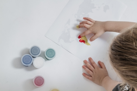 little finger: Little cute girl painting the world map with finger paint Stock Photo