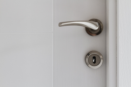 View of a door handle of an opened white door photo