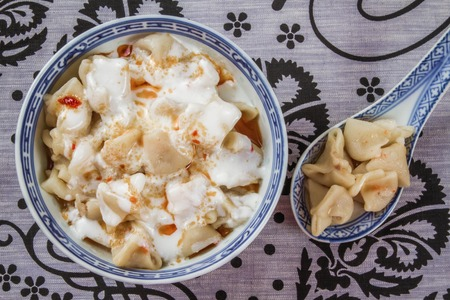 Traditional turkish ravioli in a bowl on a decorative tablecloth background photo