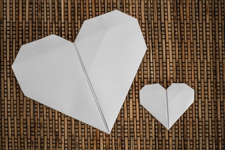 Close view of origami hearts on brown rattan tablecloth background photo