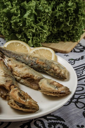 Fried mackerel in a plate on a tablecloth background photo