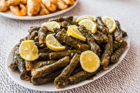 Stuffed grape leaves in a plate, near homemade pita plate