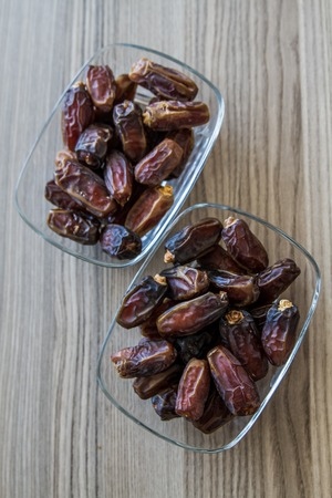 Dates, traditional Ramadan fruit in glass dishes on wooden table photo