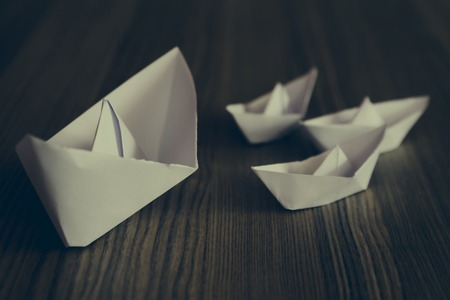 paper boat: Big and small white origami ships on wooden background