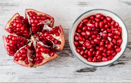 Half pomegranate and pomegranate seeds on a white wooden background