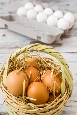 Natural brown eggs in a straw basket and white eggs in modern cardboard photo