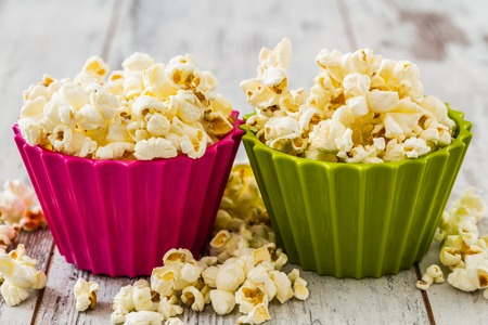 bowls of popcorn: Pile of popcorn in colorful bowls on wooden white background Stock Photo