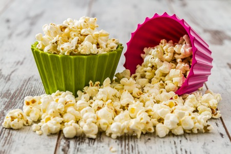 Pile of popcorn in colorful bowls on wooden white background Stok Fotoğraf - 34380585