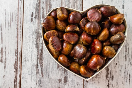 Fresh chestnuts in a heart shaped box on wooden white background