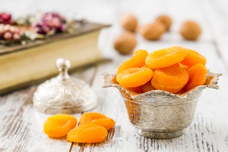 Dried apricots in traditional silver bowl on wooden white table