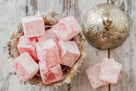 Rose flavoured Turkish delight in traditional silver bowl on wooden white background photo