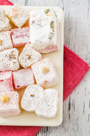 Assortment of Turkish Delight in a square plate on wooden white background photo