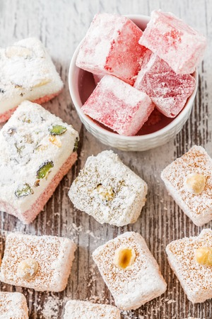 Assortment of Turkish Delight in a white bowl on wooden white background photo