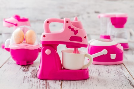 mini oven: Plastic pink kitchen toy machiness on white wooden table Stock Photo