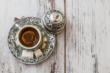 Traditional Turkish coffee in traditional silver cup on white wooden table Imagens