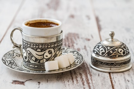 Traditional Turkish coffee in traditional silver cup on white wooden background Imagens
