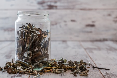 Screws and nuts in a glass can on white wooden background Stock Photo