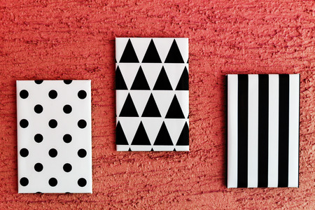 poster wall: Black and white geometrical painted canvases hanging on green wall Stock Photo