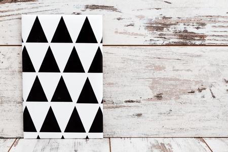 marcos redondos: Lienzos pintados geom�tricos blancos y negros en el fondo de madera blanca