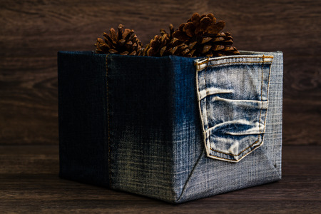 Dry pine cones in denim box on brown wooden table