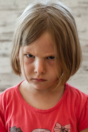 Very angry little girl in front of white wooden background
